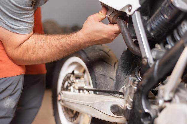 Meccanico vicino riparazione di moto nel garage di riparazione.