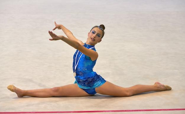 Medaglia di ginnastica di ginnastica ragazza tiene la medaglia