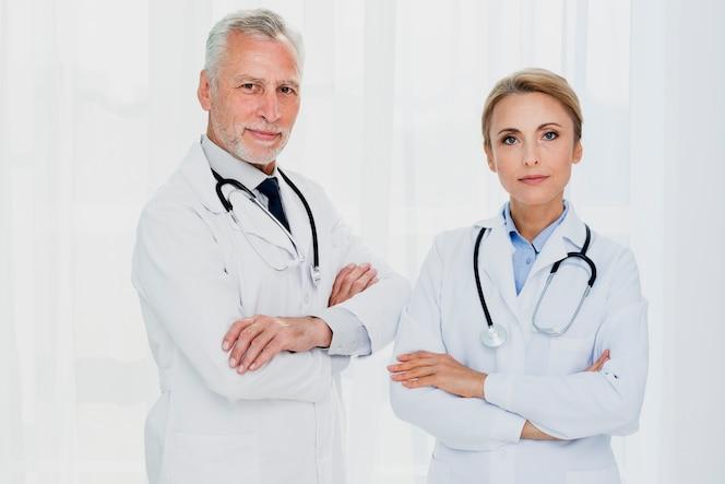 Medici che esaminano macchina fotografica con le mani incrociate