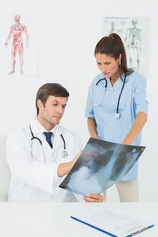 Medici che esaminano raggi x in studio medico