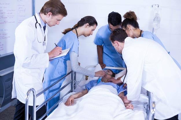 Medici che esaminano un paziente sul letto in ospedale