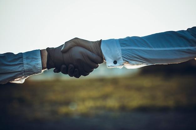 Medici che si tengono per mano insieme come colleghi che indossano guanti di gomma o lattice nero. coronavirus o concetto di protezione covid-19.