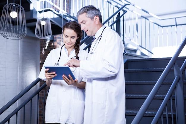 Medici che utilizzano compressa digitale sulla scala nell'ospedale