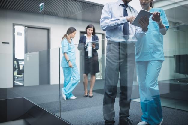 Medici e infermieri che discutono su tavoletta digitale