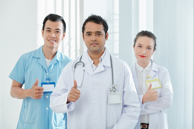 Medici felici che mostrano il pollice in su