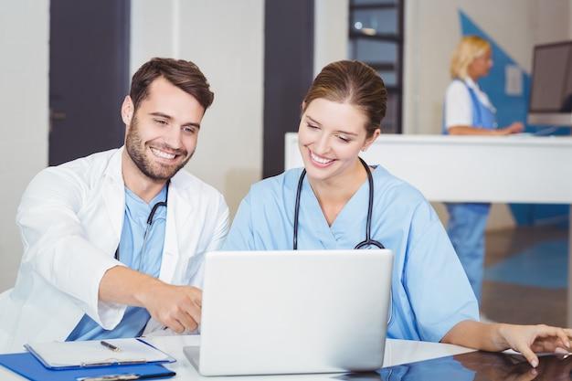 Medici felici che per mezzo del computer portatile mentre discutendo allo scrittorio