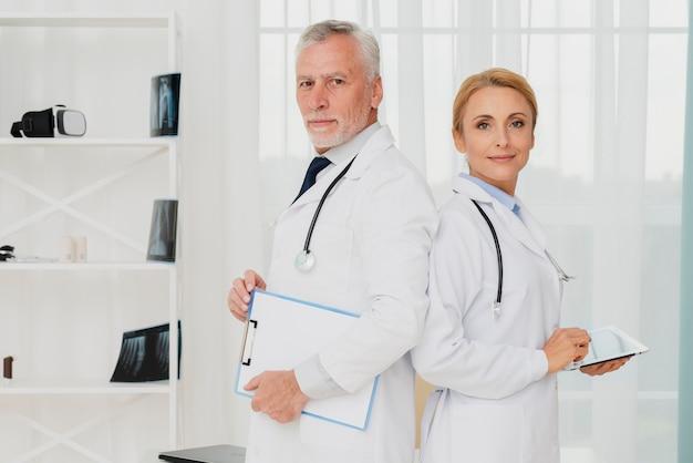 Medici in piedi schiena contro schiena