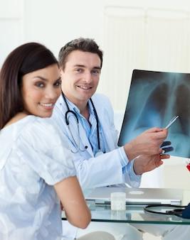 Medici sorridenti che esaminano una raggi x