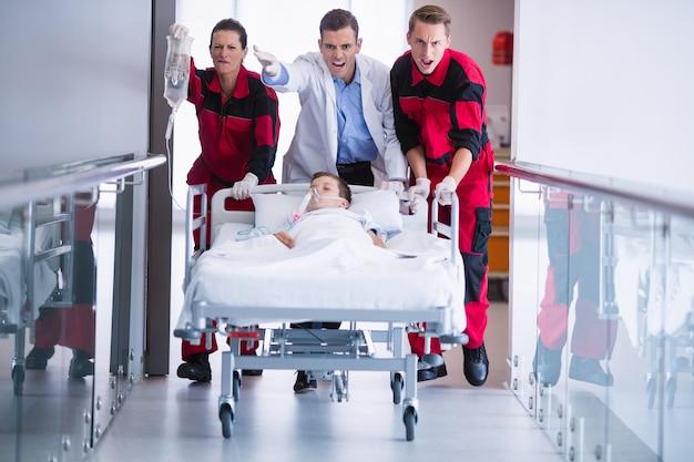 Medici spingendo il letto della barella di emergenza in corridoio