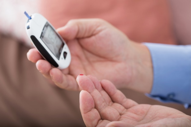 Medicina, diabete, glicemia, sanità e concetto della gente - vicino su del dito maschio con la banda di prova