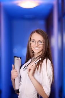 Medicina. medico femminile che sta con una cartella nell'ospedale. studente laureato. ragazza giovane e bella. abito bianco.