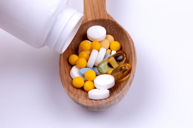 Medicina, pillole e droga in cucchiaio di legno su fondo bianco con lo spazio della copia