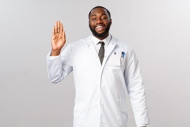 Medico afroamericano del ritratto in uniforme bianca.