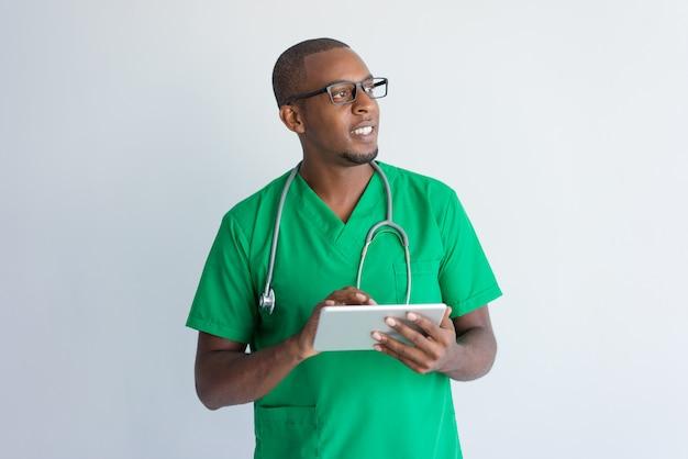 Medico afroamericano sorridente che per mezzo della compressa digitale.