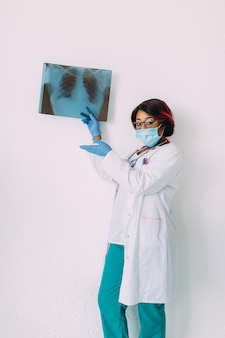 Medico afroamericano sorridente dei giovani nella radiografia medica del paziente della tenuta della maschera