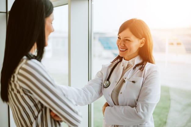 Medico allegro della donna che parla con la giovane donna in ufficio.