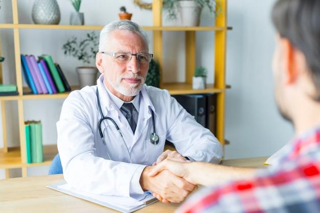 Medico amichevole che agita mano del paziente