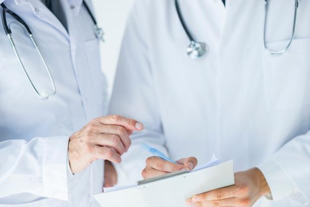 Medico anonimo che aiuta collega a scrivere prescrizione