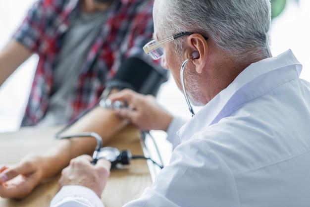 Medico anziano che misura pressione sanguigna del paziente