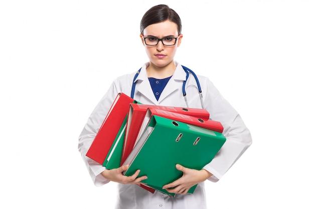 Medico arrabbiato della giovane donna con i raccoglitori della tenuta dello stetoscopio in sue mani in uniforme bianca