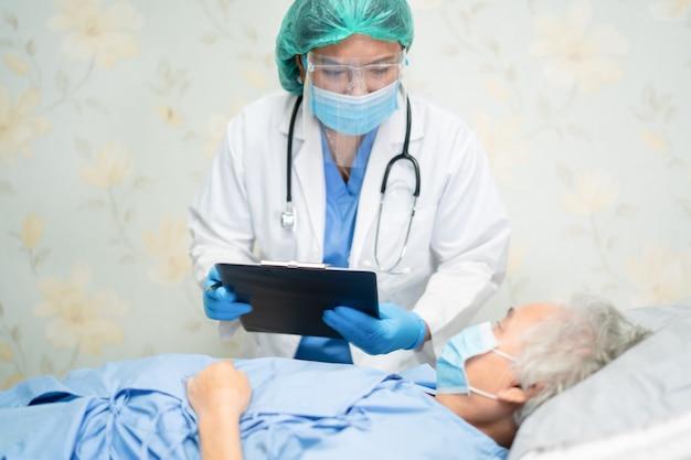 Medico asiatico che indossa uno scudo facciale e una tuta dpi per verificare la protezione del paziente covid-19 coronavirus.