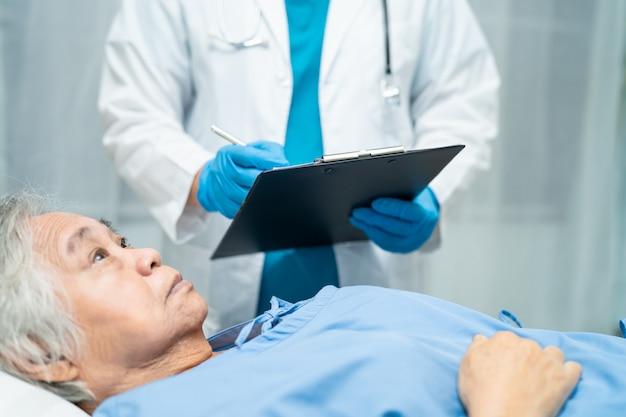 Medico asiatico che indossa uno scudo facciale e una tuta dpi per verificare la protezione del paziente covid-19