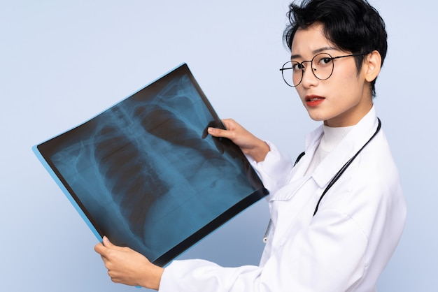 Medico asiatico che tiene una scansione dell'osso
