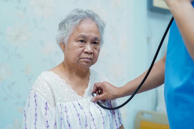 Medico asiatico del fisioterapista dell'infermiera facendo uso dello stetoscopio a controllare il paziente in ospedale.