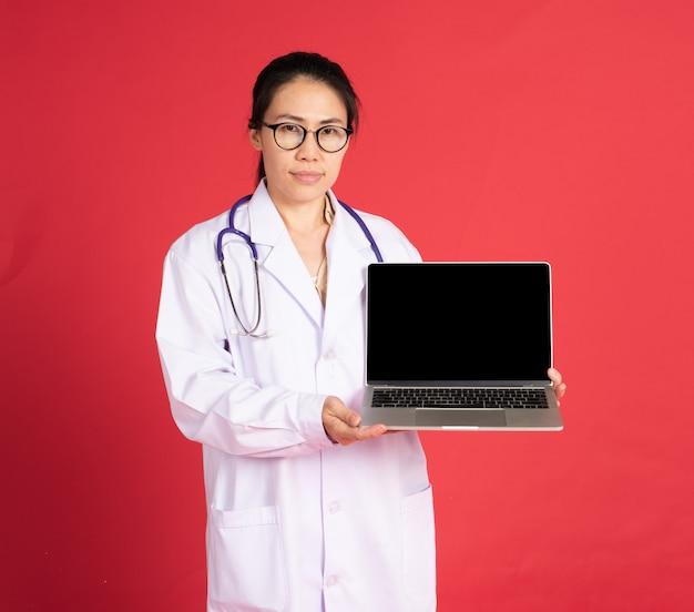 Medico asiatico della donna che per mezzo del computer portatile sulla parete rossa