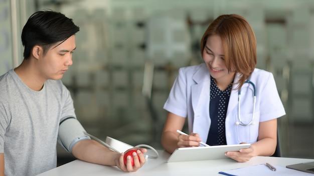 Medico asiatico della donna con la compressa che parla con paziente asiatico maschio in ufficio