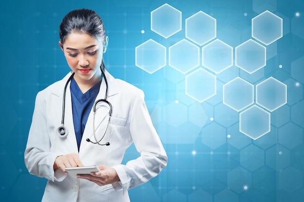 Medico asiatico della donna in camice e stetoscopio bianchi del laboratorio facendo uso della compressa
