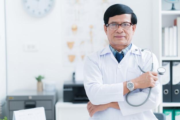 Medico asiatico maggiore che lavora nella stanza dell'esame