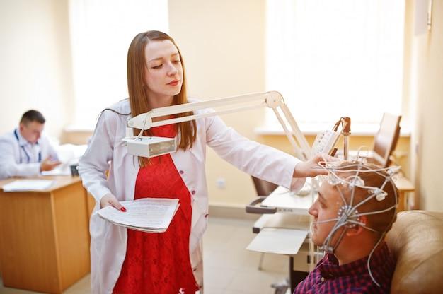 Medico attraente in camice che esamina la salute del suo paziente.