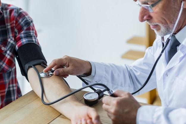 Medico barbuto che misura pressione sanguigna