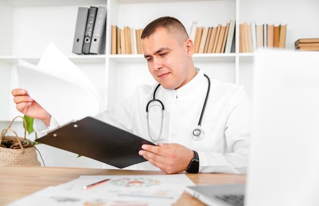 Medico bello che tiene una lavagna per appunti