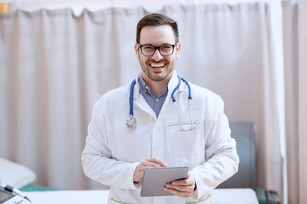 Medico caucasico allegro in uniforme bianca e con lo stetoscopio intorno alla compressa della tenuta del collo