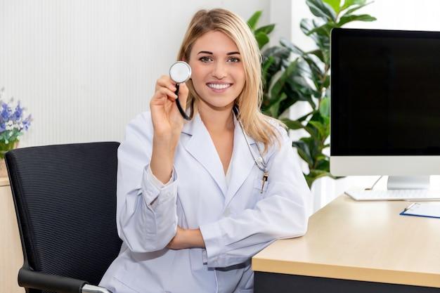 Medico caucasico astuto della donna che indossa uno stetoscopio sulla stanza di ospedale.
