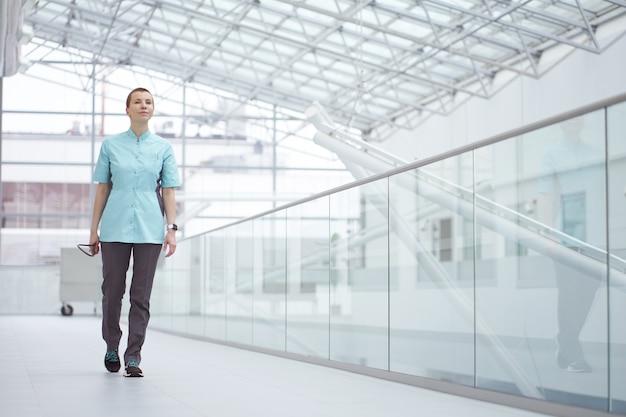 Medico caucasico della donna che cammina allegramente in corridoi bianchi della clinica