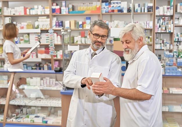 Medico che aiuta il pansioner con la scelta delle medicine.