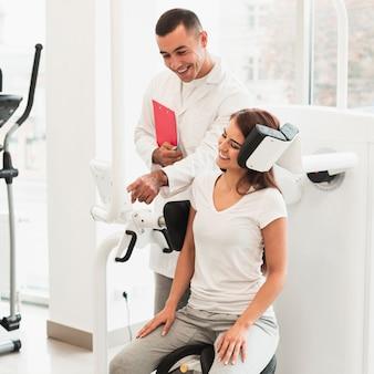 Medico che aiuta paziente femminile con un dispositivo
