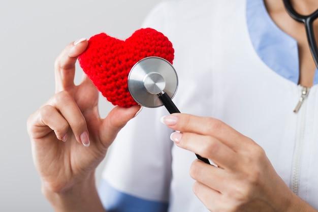 Medico che ascolta un cuore di peluche
