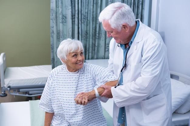 Medico che assiste il paziente anziano all'ospedale