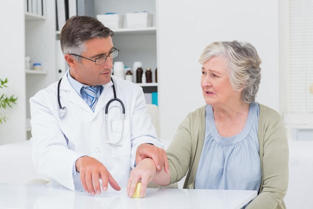 Medico che assiste il paziente per tenere il peso al tavolo