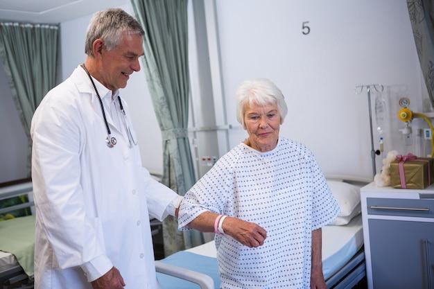 Medico che assiste paziente anziano in reparto