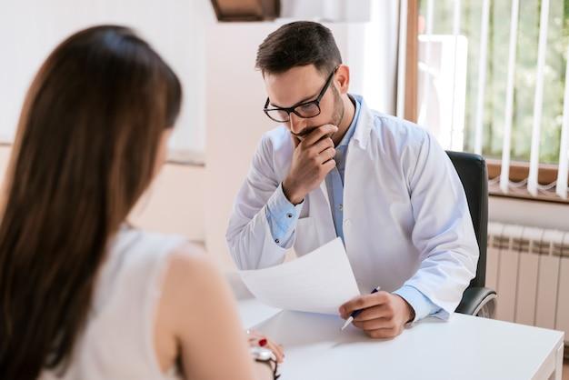 Medico che consulta e che esamina la salute del paziente della donna in clinica medica.