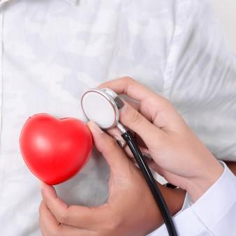 Medico che controlla il cuore rosso con la linea di ecg e stetoscopio.