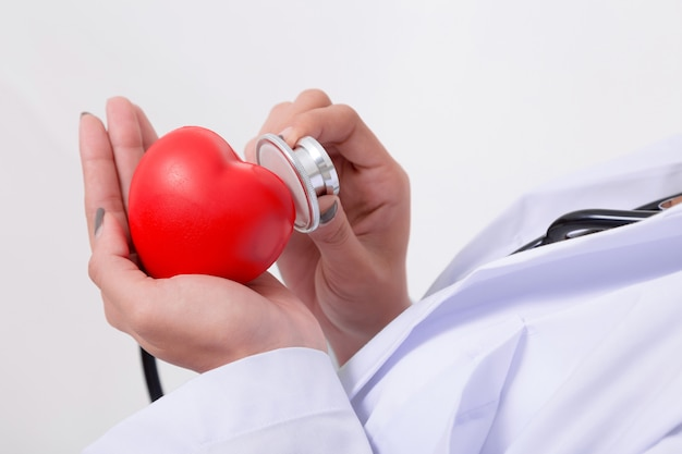 Medico che controlla il cuore rosso con la linea di ecg e stetoscopio