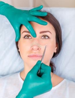 Medico che controlla il viso della donna, la palpebra prima della chirurgia plastica, la blefaroplastica.