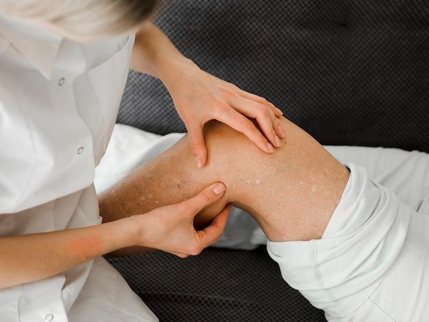 Medico che controlla la gamba del paziente