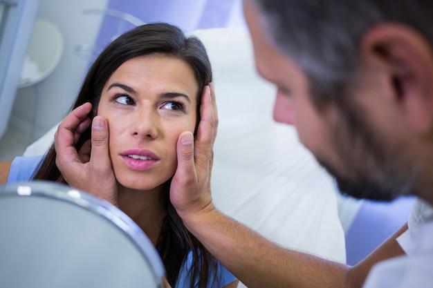 Medico che controlla la pelle dei pazienti dopo il trattamento cosmetico